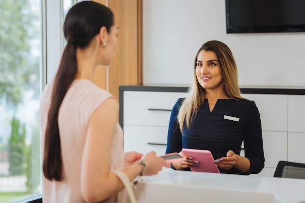 Agradable mujer amable hablando con el cliente mientras está de pie en la recepción