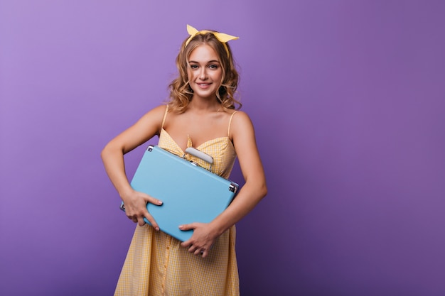 Agradable mujer bronceada que sostiene su valija azul. modelo de mujer optimista con cinta amarilla posando con equipaje en violeta.