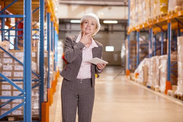 Agradable mujer pensativa sosteniendo su barbilla mientras piensa en el problema de logística