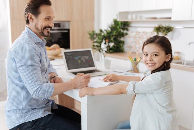 Agradable padre joven sentado en el mostrador de la cocina, sosteniendo un lápiz y listo para ayudar a su linda hija con su tarea en casa mientras ella mira al frente y sonríe