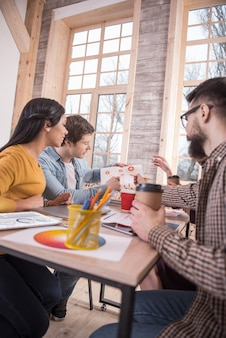 Agradable trabajo en equipo. jóvenes inteligentes encantados que se sientan a la mesa e intercambian sus ideas mientras disfrutan de su trabajo en equipo