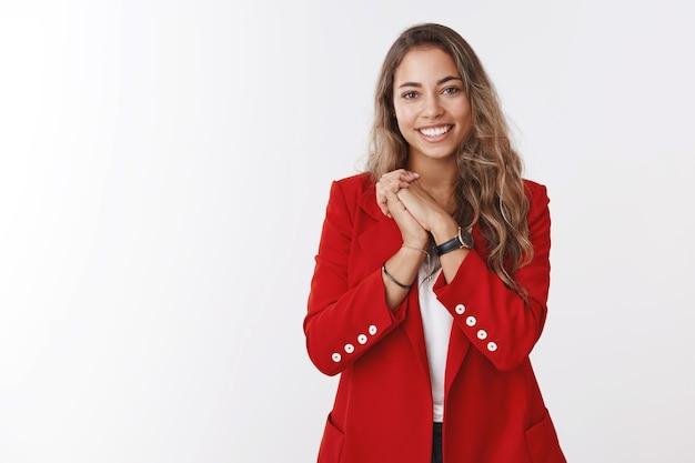 Agradecida y complacida joven hermosa europea de pelo rizado, vestida con una chaqueta roja presionando las palmas juntas agradecidas, apreciando el lindo gesto romántico, sonriendo recibiendo felicitaciones de cumpleaños
