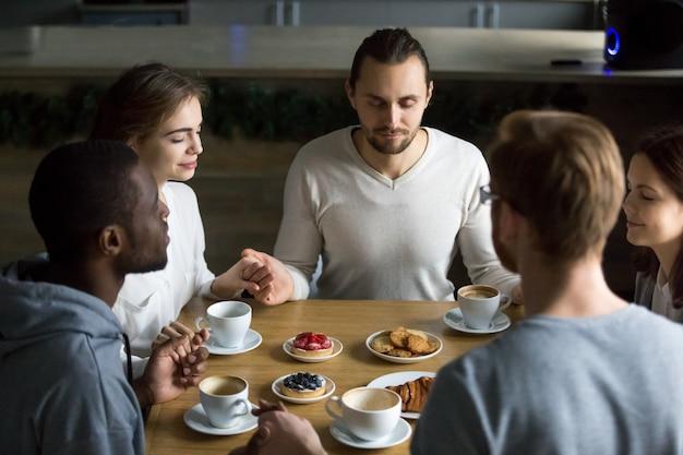 Agradecidos amigos multirraciales sentados juntos en la mesa del café diciendo gracia