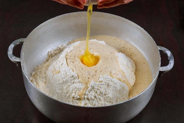 Agregar huevo a la masa de levadura para hacer pan