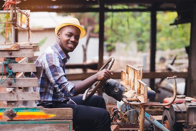Agricultor africano conduce pequeño tractor en el campo