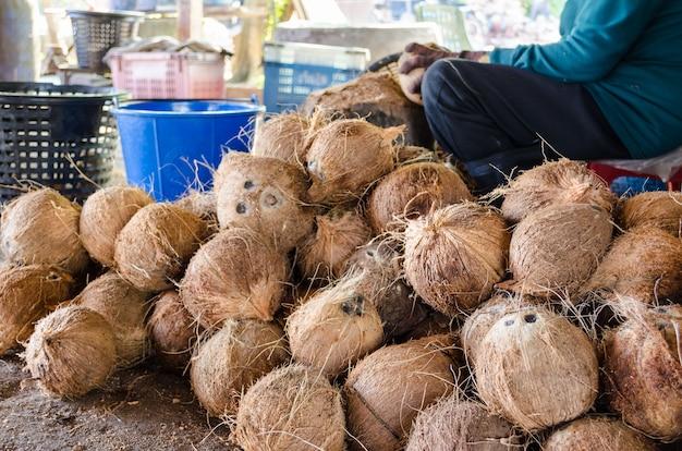 Agricultor cortando cáscara de coco para procesar productos agrícolas en una pequeña fábrica en tailandia.