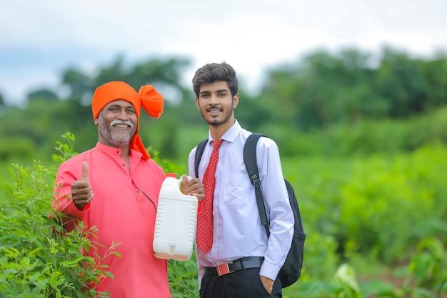 Agricultor indio con agrónomo en el campo, agricultor y agrónomo mostrando botella de fertilizante