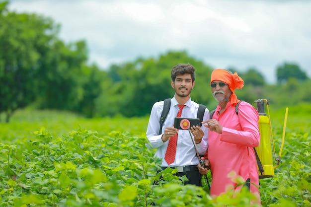 Agricultor indio discutiendo con un agrónomo en la granja y recopilando información