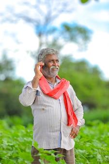 Agricultor indio hablando por teléfono móvil en el campo agrícola