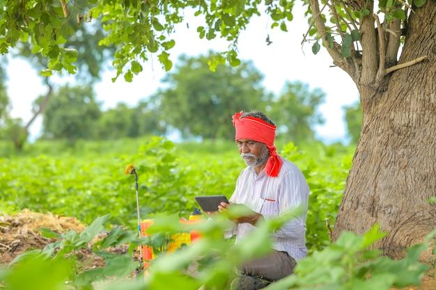 Agricultor indio mediante teléfono móvil en el campo agrícola