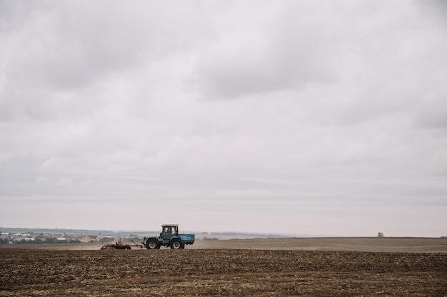 Agricultor en tractor preparando la tierra con cultivador de semillero en tierras de cultivo. el tractor ara un campo. trabajos agrícolas en procesamiento, cultivo de tierra. agricultores preparando la tierra y fertilizando. agrícola