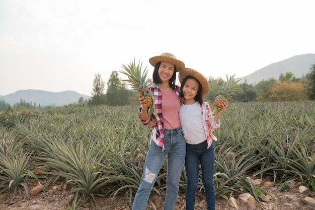 La agricultora asiática ve el crecimiento de la piña en la granja, el concepto de industria agrícola.