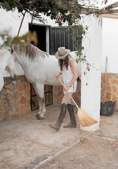 La agricultora limpiando sus establos de caballos