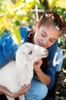 La agricultora sosteniendo una oveja bebé