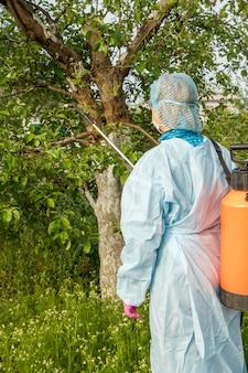 La agricultora con traje de protección está rociando manzanos de enfermedades fúngicas o alimañas con un rociador a presión y productos químicos en el huerto de primavera.
