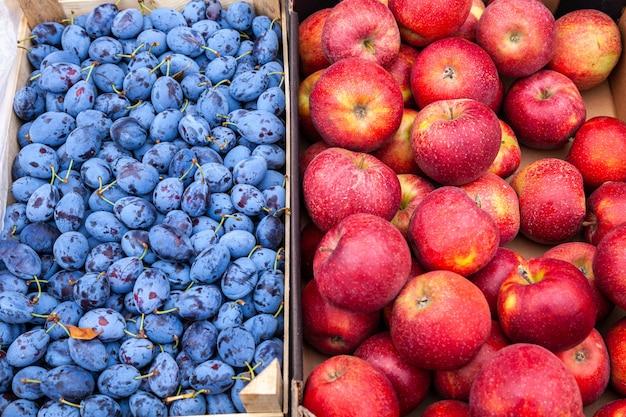 Los agricultores frescos manzanas y ciruelas en el mercado local al aire libre.