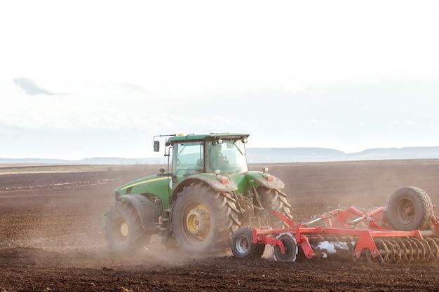 Agricultura, tractor preparando tierras con cultivador de semillero como parte de las actividades previas a la siembra a principios de la temporada de primavera de trabajos agrícolas en tierras de cultivo