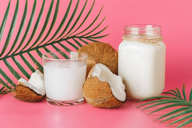 Agrietado coco y leche de coco en vidrio sobre fondo rosa brillante