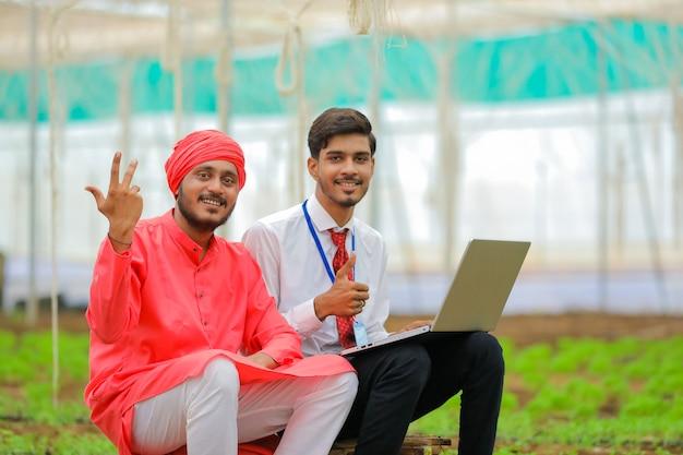 Agrónomo y agricultor indio joven en invernadero