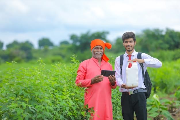 Agrónomo y agricultor indio mostrando botella de fertilizante en el campo