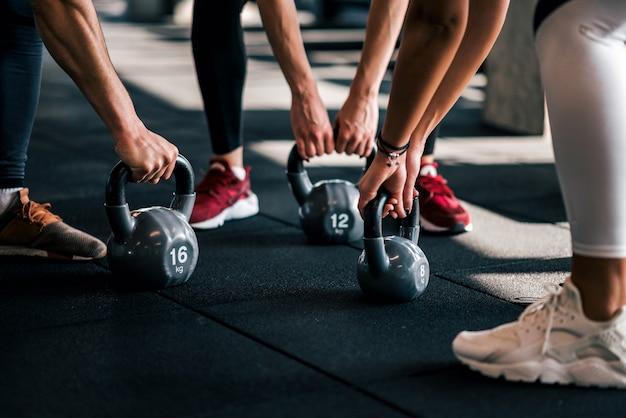 Agrupe a la gente en la ropa de deportes que lleva a cabo pesas de gimnasia durante entrenamiento en el gimnasio, ángulo bajo, primer.