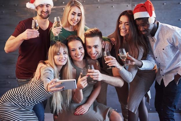 Agrupe a hermosos jóvenes haciendo selfie en la fiesta de año nuevo, los mejores amigos, niñas y niños, divirtiéndose, posando a personas de estilo de vida emocional. sombreros santas y copas de champaña en sus manos