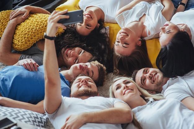 Agrupe a hermosos jóvenes haciendo selfie tirado en el piso, mejores amigos, niñas y niños juntos divirtiéndose, posando un estilo de vida emocional