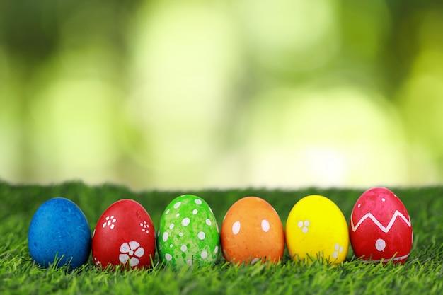 Agrupe los huevos de pascua hermosos coloridos y adornados en hierba verde en naturaleza con el fondo verde del bokeh. imagen publicitaria concepto de festival de pascua con espacio libre.