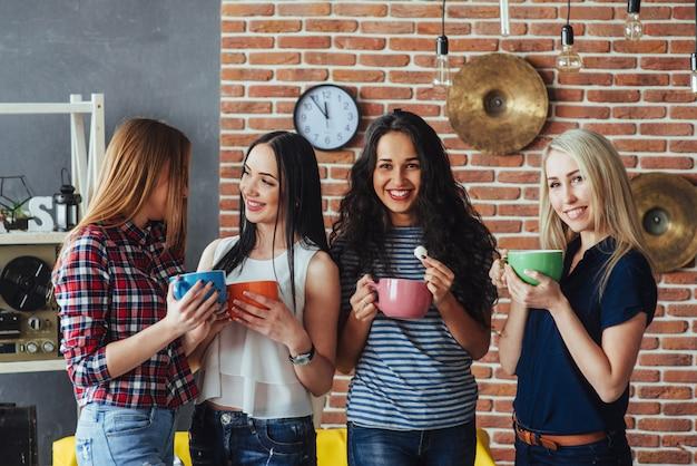 Agrupe a jóvenes hermosos disfrutando de una conversación y tomando café, las mejores amigas juntas divirtiéndose, posando un estilo de vida emocional