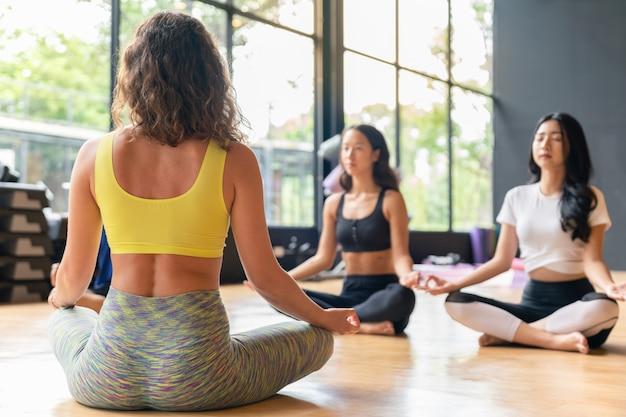 Agrupe a la mujer que practica yoga y medita en la postura del loto en el gimnasio, el deporte y el club de entrenamiento.