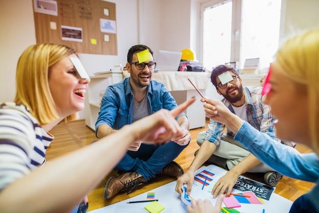 Agrupe a sus colegas sentados en círculo, jugando y divirtiéndose.