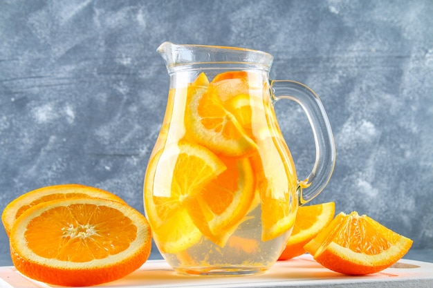 Agua anaranjada del detox en una jarra en un fondo concreto gris. comida sana, bebidas.