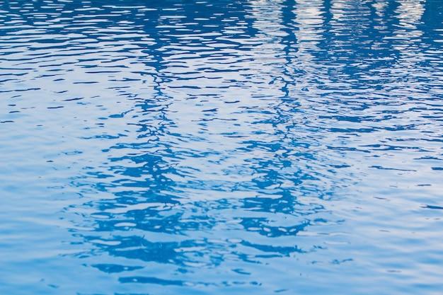 Agua azul con olas en la piscina en la mañana.