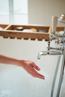 El agua brota del grifo en las manos de la niña. el baño es luminoso.