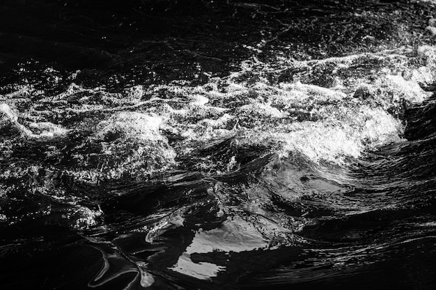 Agua burbujeante con espuma y salpicaduras. foto en blanco y negro. foto de alta calidad
