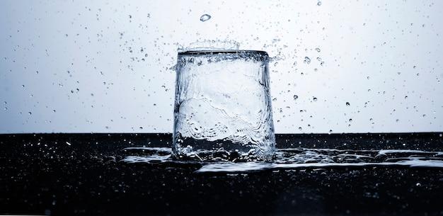 Agua clara en vaso con gotas de agua