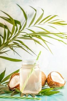 Agua de coco y cocos sobre un fondo con hojas tropicales