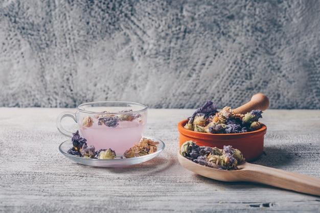 Agua de color púrpura en una taza con té de flores secas en un tazón y cuchara vista lateral sobre un fondo blanco de madera y gris. espacio libre para su texto