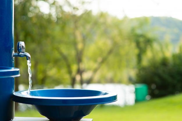 El agua corre en el parque en el grifo azul