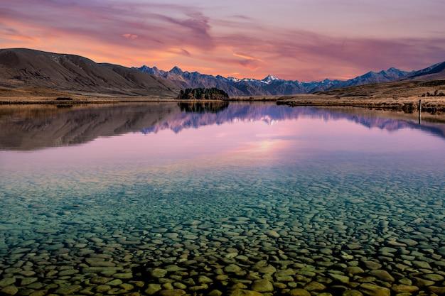 Agua cristalina transparente que muestra las rocas en el fondo del lago con reflejos de montaña al atardecer