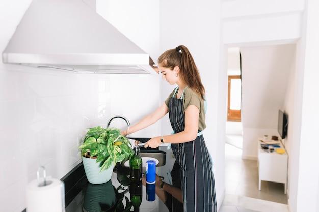 Agua de relleno de la mujer joven en la cacerola de la salsa en la cocina