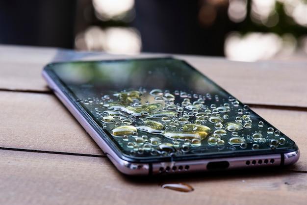 Agua derramada en el teléfono inteligente gotas de agua en pantalla móvil