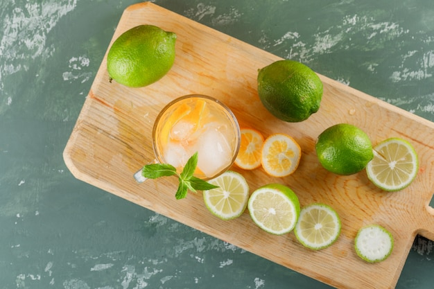 Agua de desintoxicación helada con naranja, limas, menta, tabla de cortar en una taza de yeso, vista superior.