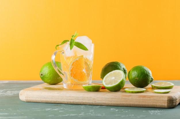 Agua de desintoxicación helada en una taza con naranja, limas, menta, vista lateral de la tabla de cortar sobre yeso y fondo amarillo