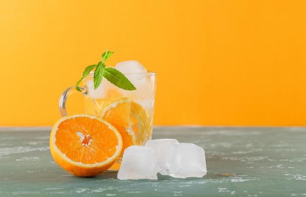 Agua de desintoxicación helada en una taza con naranja, vista lateral de menta sobre yeso y fondo amarillo