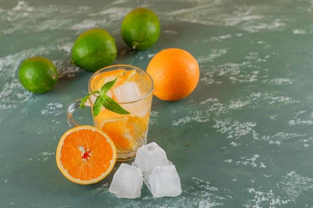 Agua de desintoxicación helada en una taza con naranjas, menta, limas, vista de ángulo alto sobre una superficie de yeso