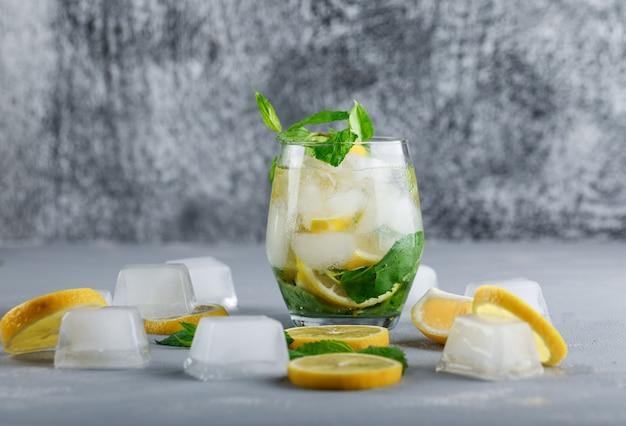 Agua de desintoxicación helada en un vaso con vista lateral de limón y menta sobre superficie gris y grunge