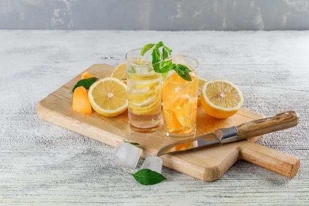 Agua de desintoxicación helada en vidrio con naranjas, limones, menta, cuchillo, tabla de cortar, ángulo de visión alto sobre fondo sucio y yeso
