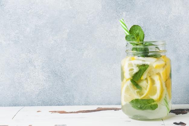 Agua dulce en jarra con limón, pepino y menta en mesa de madera. copia espacio