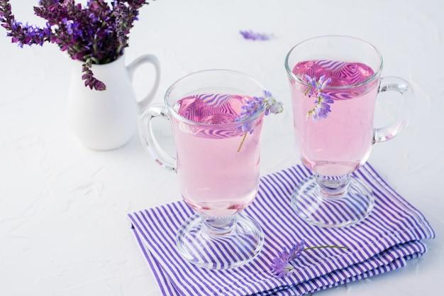Agua dulce con lavanda en vasos y un ramo de flores en una jarra sobre la mesa. cóctel aromático de lavanda. copia espacio